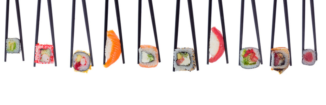 A lot of sushi and rolls in black chopsticks isolated on white background