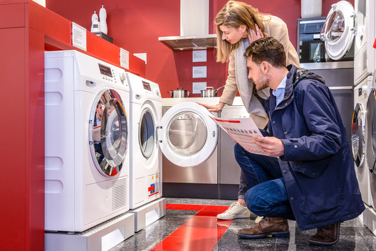 Couple Choosing Washing Machine At Hypermarket