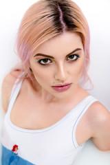 Seductive woman with pink hair and piercing looking at camera