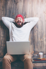 Need coffee for wake up. Yawning bearded man with laptop computer sitting over wooden background.