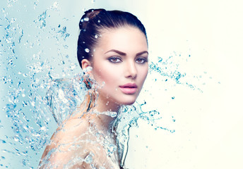 Beauty spa woman under splash of water over blue background