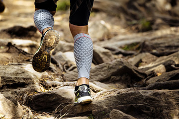 Wall Mural - athlete runner runs rocks in mountain. closeup of legs compression socks and sneakers
