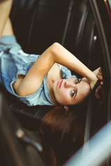 Girl lying on leather seat of car. tinted photo