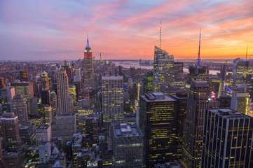 Bright golden pink sunset view of the Midtown Manhattan New York City skyline looking south