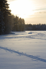 Ski tracks in the snow. The tracks are made in the deep snow on a lake ice. Image taken during sunset in Finland on a cold winter day.