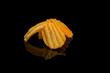 Potato chip on black surface closeup reflection detail