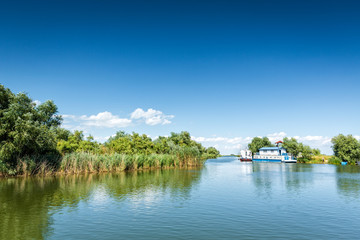 Typical Danube Delta landscape with lakes, canals and lush vegetation on a clear sunny day, in Gura Portitei resort, Romania