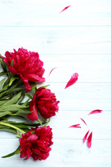 Bouquet of red peony flowers on a white wooden table