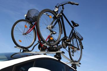 Zwei Fahrräder auf dem Dach eines weissen Autos montiert