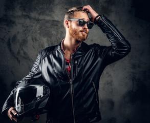 Redhead male holds motorcycle helmet.