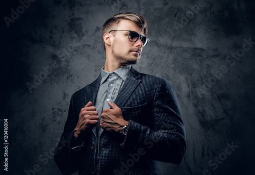 a2fd6c94dde0 A man in a suit and sunglasses on grey background.