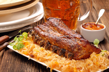 Fried pork ribs with herbs on wooden background