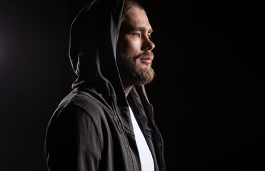 Portrait of a Man in a hoodie with a hood thrown over his head on a black background