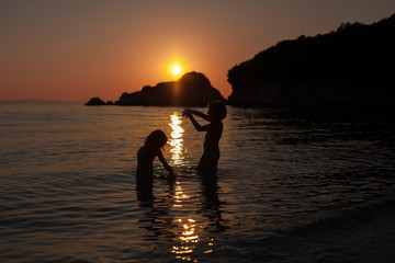Two girls playing on the beach in sea sunset. Silhouette sunset