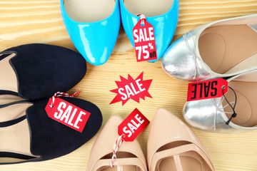 Sale concept. Set of female shoes on wooden table, flat lay