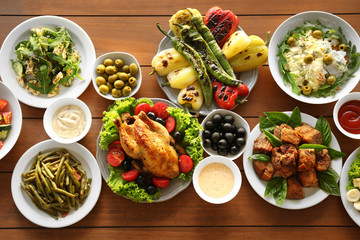 Plates with different salads and meat on table