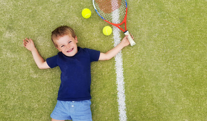 A young blond boy smiling and laying on a tennis court, with racket and balls.