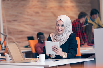 Young Arabic business woman wearing hijab,working in her startup office. Diversity, multiracial concept.