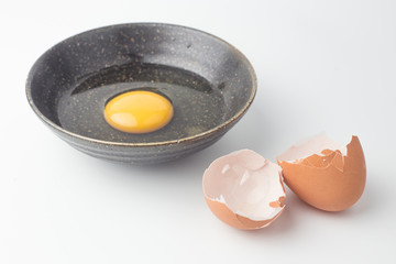 One egg yolks in black bowl and broken egg shells