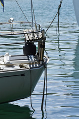 Boat stern with railing and ropes disappearing under calm water surface.