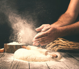 Spoed Fotobehang Bakkerij Man preparing bread dough on wooden table in a bakery