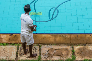 The attendant cleans the pool bottom with a vacuum cleaner.