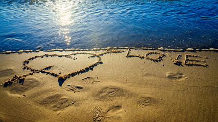 Heart and arrow drawn on sand
