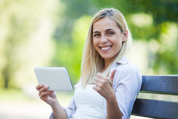 Young happy woman is sitting in park and using digital tablet.