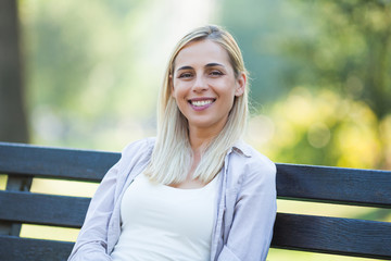 Young happy woman is sitting and relaxing in park.