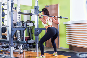 Fit woman doing squat with barbell in the gym.