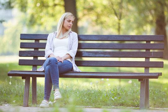 Lonely woman sitting in park in despair.