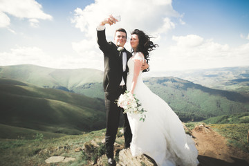 Just married couple on top of the mountain taking selfie picture