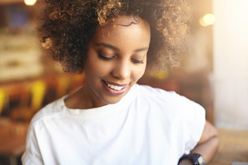 Close up of good-looking African woman with curly hair dressed in white t-shirt, spending free time at cafeteria, looking down with shy cute smile, showing her white teeth, against blurred background