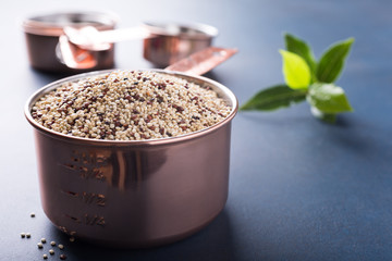 Mixed raw quinoa, South American grain, in copper measuring cup with bay laurel leaves on blue background. Healthy and gluten free food. Copy space.