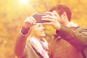 couple taking selfie with smartphone in park