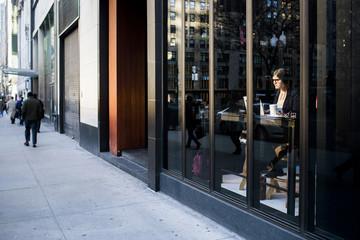 Businesswoman sitting at coffee shop seen through glass window