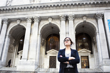 Confident businesswoman standing against New York Public Library