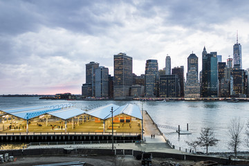 View of basketball court against East River and buildings against cloudy sky