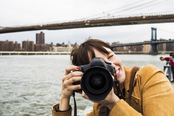 Smiling woman with camera against Brooklyn bridge and East River