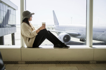 Young woman holding disposable coffee cup and waiting at airport