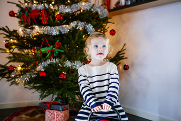 Girl playing against Christmas tree at home