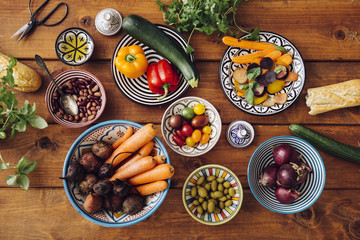 Assorted vegetables in bowls on wooden table