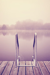 Vintage toned old wooden pier with a ladder on a foggy morning.
