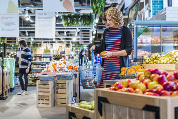 Woman buying oranges while carrying shopping basket in supermarket