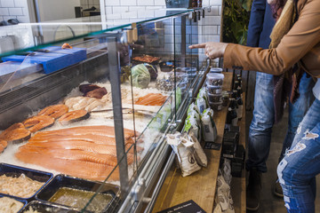 Midsection of woman pointing at seafood in supermarket
