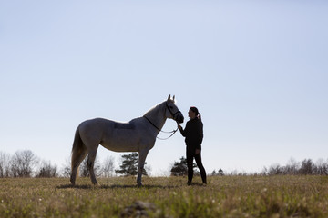 Woman looking at horse while standing on field against clear sky
