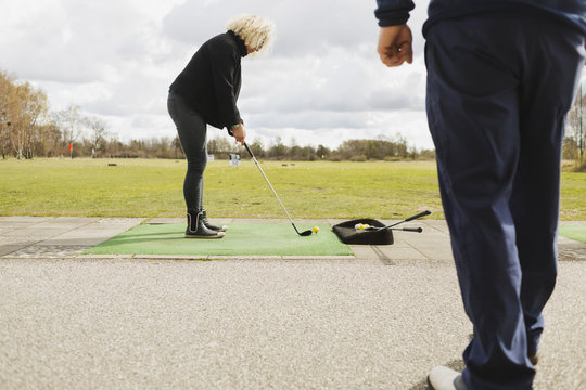 Mature woman practicing golf at driving range