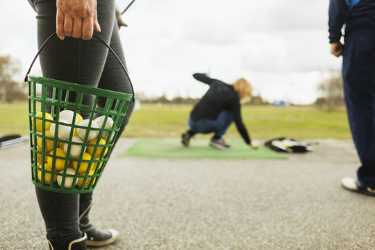 Close-up of woman holding basket filled with golf balls