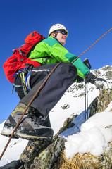 Mann klettert angeseilt im verschneiten Gebirge