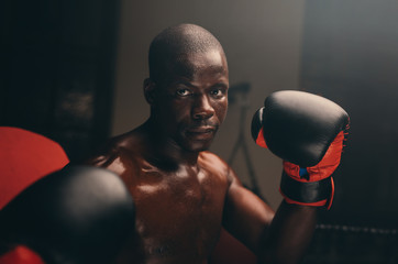 Serious strong young boxer with gloves up
